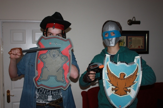 Eldest son, on the left, is dressed in a fushion of Cowboy hat, meets Jack Sparrow pirate head band with hair attachments & pirate sword, meets Lego bear shield!  Youngest son is dressed in a fushion of Teenage Mutant Ninja Turtles mask, meets Knights facial armour, meets Lego Eagle shield, meets Laser tag gun!